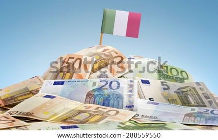 The national flag of Italy sticking in a pile of mixed european banknotes.(series) - stock photo