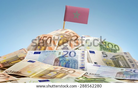 The national flag of Morocco sticking in a pile of mixed european banknotes.(series) - stock photo