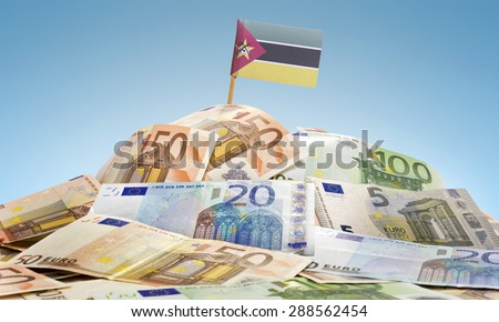 The national flag of Mozambique sticking in a pile of mixed european banknotes.(series) - stock photo