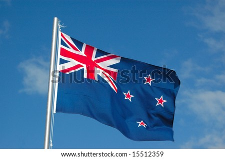 The national flag of New Zealand in blue with red and white stars blowing in the wind against a blue sky background
