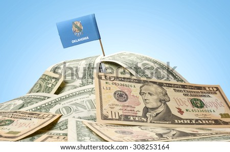 The national flag of Oklahoma sticking in a pile of american dollars.(series) - stock photo