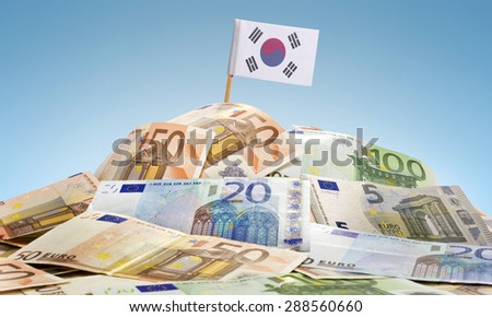 The national flag of South Korea sticking in a pile of mixed european banknotes.(series) - stock photo