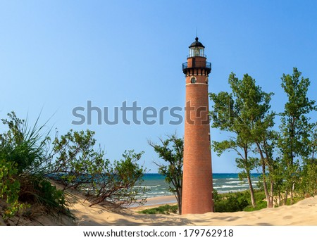 The natural red brick lighthouse  at Michigan's Little Sable Point is viewed through sand dunes overlooking Lake Michigan surf. - stock photo
