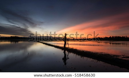 The Nature Lover. Silhouette of unknown photographer taking a beautiful sunset.Landscape composition