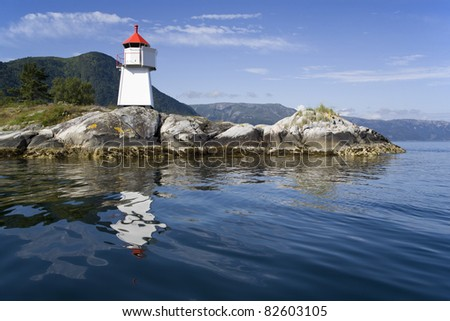 The nature of summer Norway. Reflections in fine pure water. Beacon on rocky coast - stock photo
