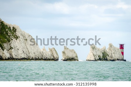 The Needles is a row of three distinctive stacks of chalk that rise out of the sea off the western end of the Isle of Wight, UK - stock photo