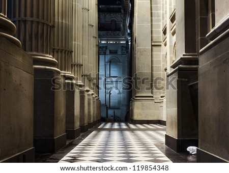 The neo-Renaissance colonnade at the entrance to the State Library of Victoria in Melbourne, Australia, at night. Plastic bag in foreground and  bicycle in background show a contemporary context. - stock photo