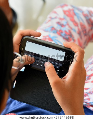 The new generation is addicted to technology. Traditional letters and cards are redundant in the age of internet and cell phones. An Indian teenage girl is sending message from her mobile phone. - stock photo
