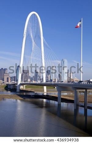 The new Margaret Hunt Hill Bridge that crosses the Trinity River with downtown Dallas, Texas in the background. The bridge uses a unique design of a 400-foot steel arch and cables. - stock photo