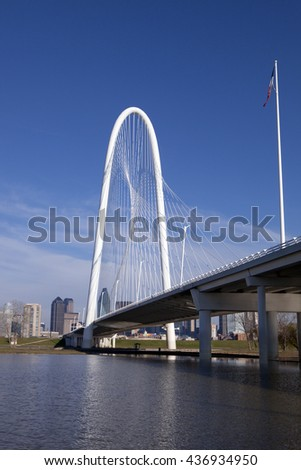 The new Margaret Hunt Hill Bridge that crosses the Trinity River with downtown Dallas, Texas in the background. The bridge uses a unique design of a 400-foot steel arch and cables.