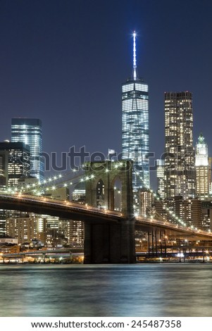 The New York City skyline at night w Brooklyn Bridge and Freedom tower - stock photo