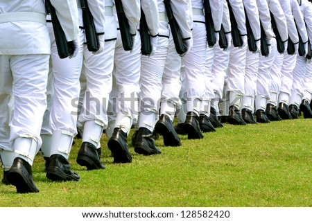 The New Zealand Military Navy wear a plain white uniform, black soldier boots, carry guns and march in a row during an army parade - stock photo
