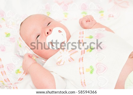 The newborn child sucks a dummy - stock photo