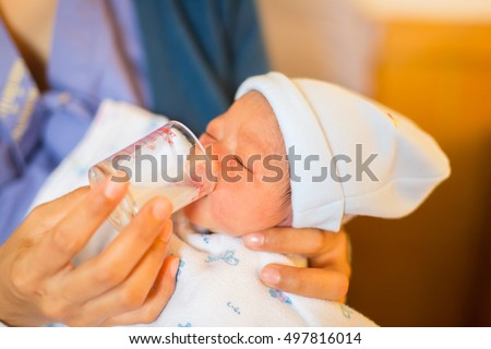 the newborn is sucking milk from cup. because mother does not have milk from breast.