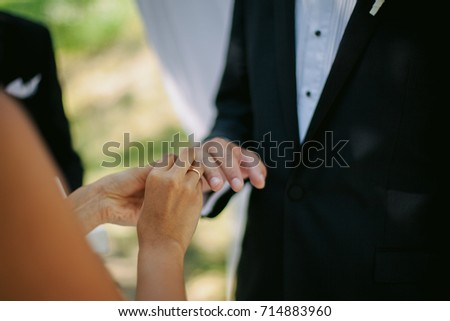 The newlyweds exchange rings, near the wedding arch, at the wedding ceremony. wedding rings and the hands of the bride and groom. young wedding couple at ceremony. marriage. soft focus