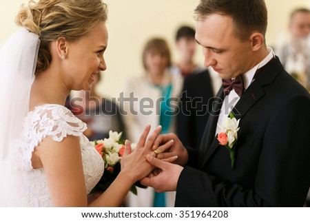 The newlyweds exchanged gold rings at a wedding ceremony in the presence of guests and relatives. Creating a new family. - stock photo