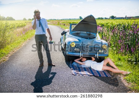 The newlyweds have a car breakdown. The bride is trying to fix it while the groom is calling the repairman. - stock photo