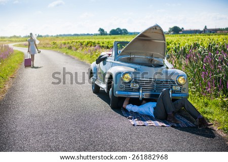 The newlyweds have a car breakdown. The groom is fixing it while his bride is hitting the road with her suitcase - stock photo