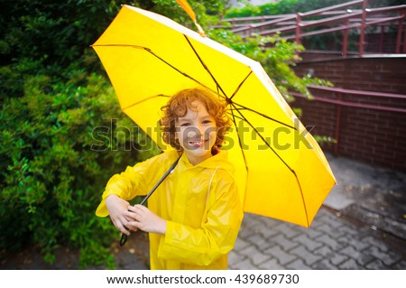 The nice fellow of 8-9 years under a yellow umbrella. The boy in a bright yellow raincoat holds a big umbrella in hand. The child looks in the camera with a smile. It likes to walk under a drizzle. - stock photo