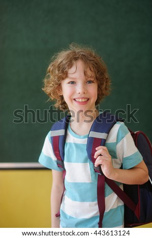 The nice schoolchild stands in the class near a blackboard. Behind shoulders at it a school backpack. The school student looks in the camera and smiles. The boy has fair curly hair and blue eyes.