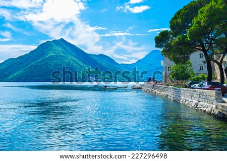 The nice views on the high mountains around the narrow bay, medieval architecture and bright blue sea makes Perast popular among tourists, Montenegro. - stock photo