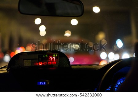 The night scene of the view from the cab with taxi meter display in Thailand