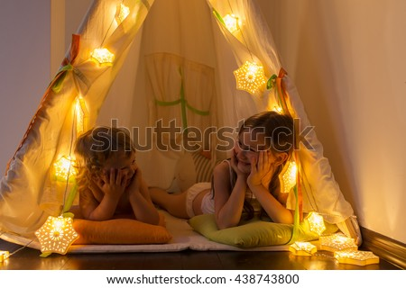 The night. Two little sisters indulge in the tent. Houses, before going to bed, bedside lamp - stock photo