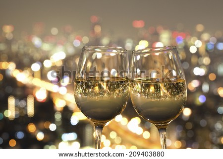 The Night View Of The City Reflected In The Glass Of Wine - stock photo