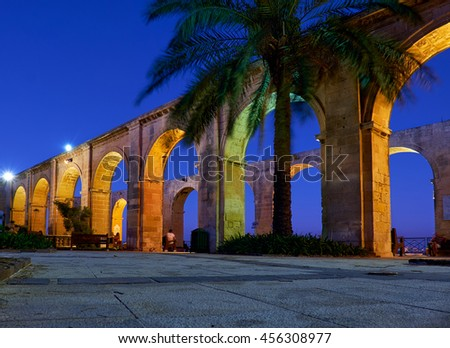 The night view of the terraced arches and the palm tree in the Upper Barrakka Gardens, Valletta, Malta
