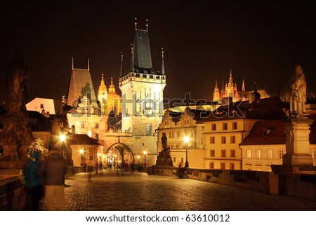The night View on bright Prague St. Nicholas' Cathedral with the Bridge Tower and Castle - stock photo