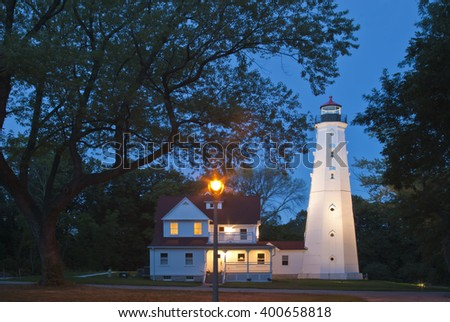The North Point Lighthouse sits on the Milwaukee bluff looking over Lake Michigan, newly refurbished it's lights again blaze as day turns to dusk. - stock photo