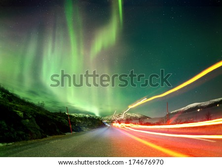 The Northern Lights in Norway landscape with red light trails on a road. - stock photo