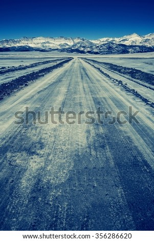 The Nowhere Road and the Mountain Range. Desert Road Somewhere in California, United States. Vintage Blue Color Grading - stock photo