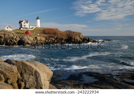 The Nubble Lighthouse on its rocky island in winters late afternoon light and early moonrise - stock photo
