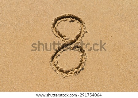 The number 8 drawn on sand at the beach, holiday concept background. - stock photo