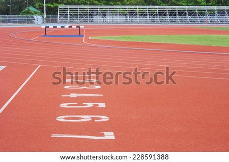 the number on the running lane in the outdoor stadium with grandstand background - stock photo