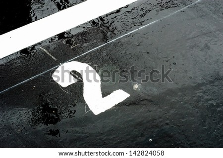 "The number ""2"" printed on the wet road. closeup - stock photo"