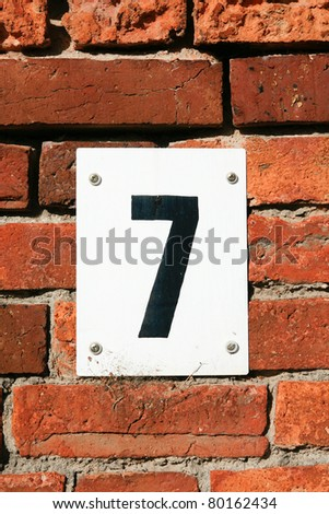 The number seven attached to a brick car park wall - stock photo