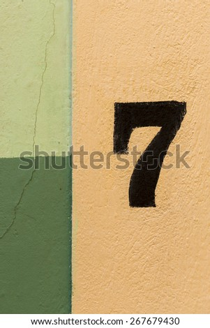 The number seven painted on a coulourful wall of yellow and green patches. - stock photo