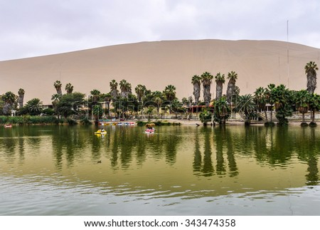 The oasis between the dunes of Huacachina in the coastal desert of Peru - stock photo