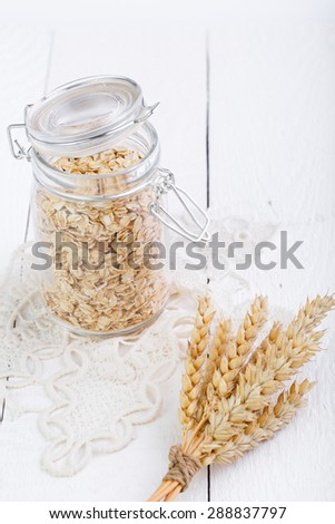 The oat flakes in glass jar on lace napkin.