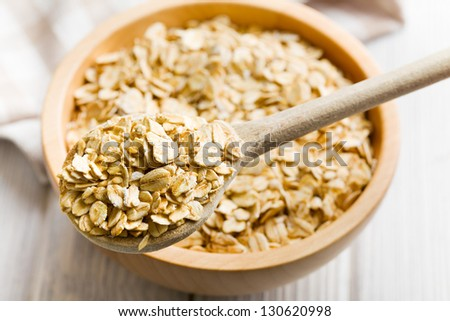 the oat flakes on a wooden spoon - stock photo