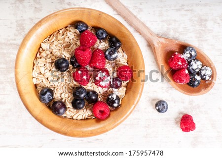 The oat flakes with red and blue berries in the wooden dish - stock photo