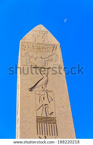 The Obelisk of Theodosius at Sultanahmet park and the moon in the blue sky. It is the Ancient Egyptian obelisk of Pharaoh Tutmoses III. - stock photo