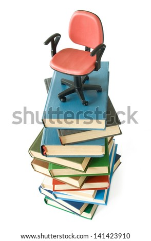 The office chair from red imitation leather on big book pile isolated on white background/ Concept - stock photo