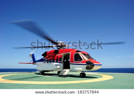The offshore helicopter at the oil platform - stock photo