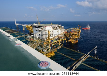 The offshore oil rig and supply boat in the gulf of Thailand - stock photo