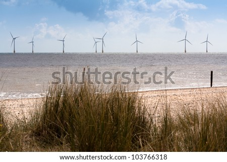 The offshore wind turbines at Scroby Sands, Caister, Norfolk, UK. Dune grass and beach in foreground. Copyspace available. - stock photo