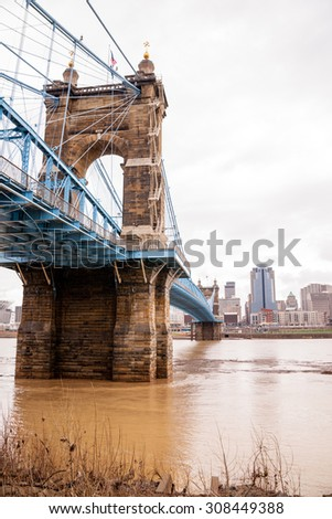 The Ohio River is at flood stage as it passes underneath a historical suspension bridge - stock photo