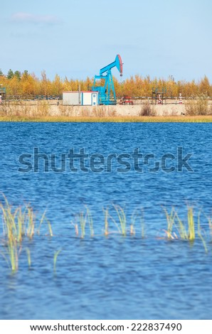 The oil pump on the bank of the lake. - stock photo
